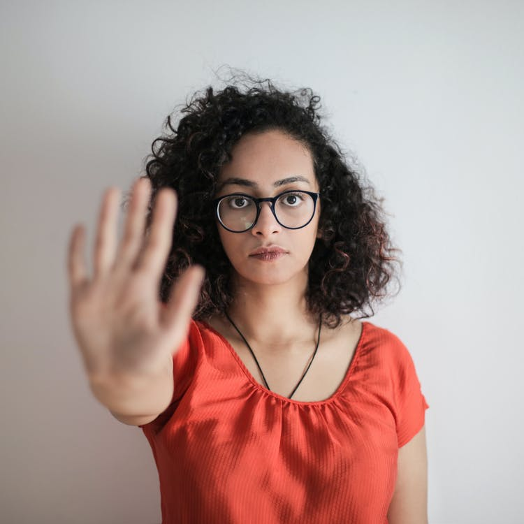 Portrait Photo of Woman in Red Top Wearing Black Framed Eyeglasses Holding Out Her Hand in Stop Gesture