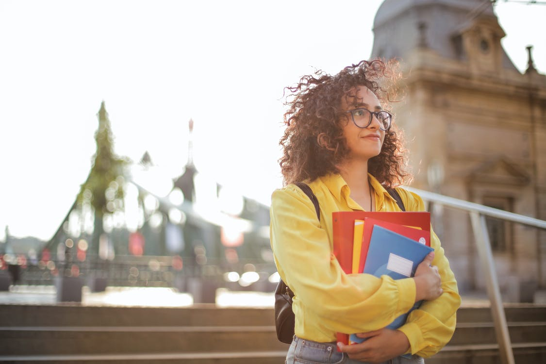 Selective Focus Photo of Woman in Yellow Long Sleeve Shirt and Glasses Carrying Folders