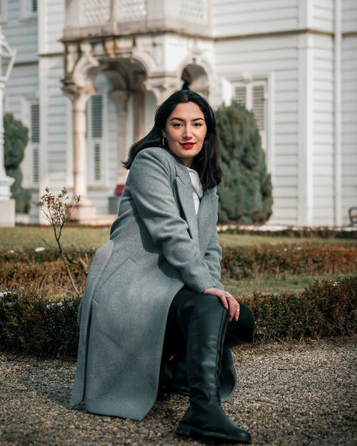 Selective Focus Photo of Woman in Gray Coat Squat Posing
