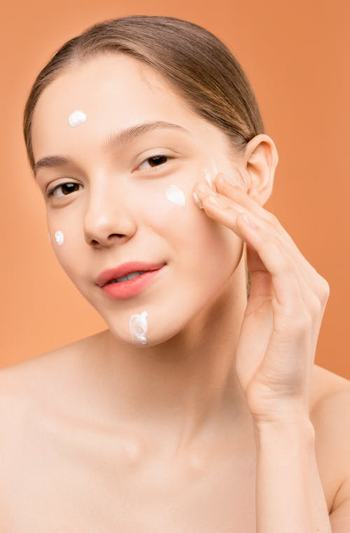 Woman Applying Facial Cream on Her Face