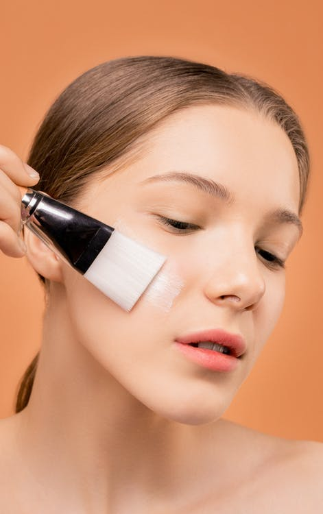 Woman Applying Moisturizer on Her Face Using Brush