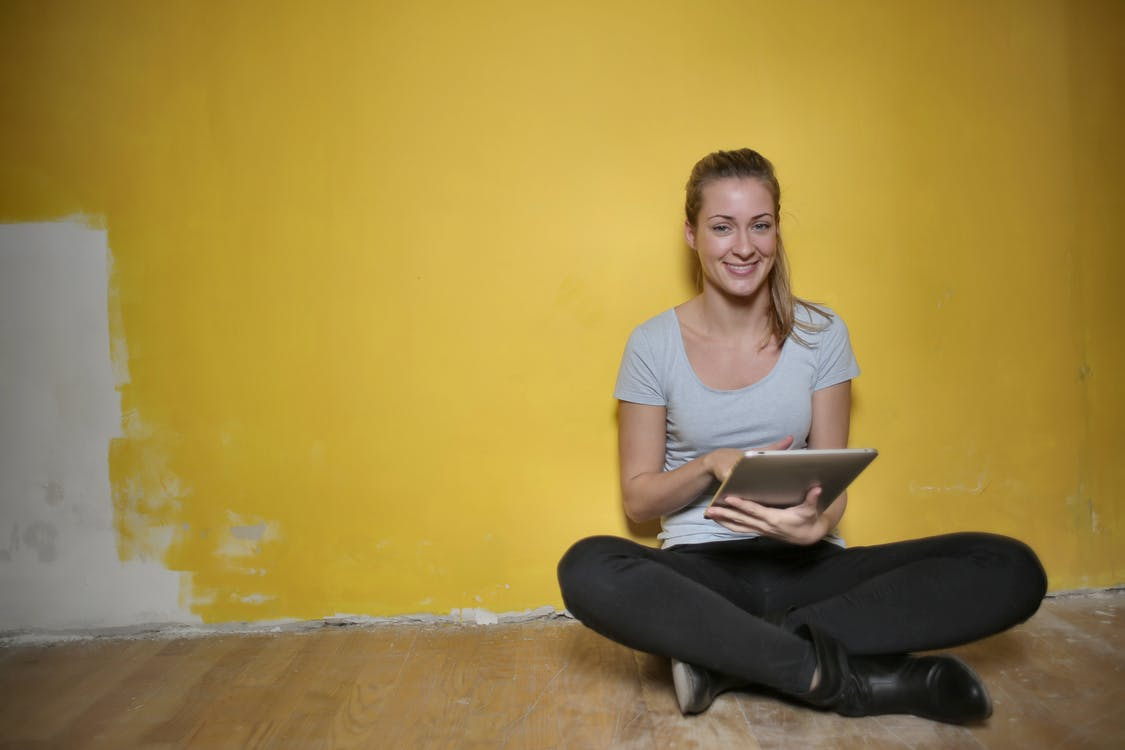 Woman Sitting On Wooden Floor Using Tablet