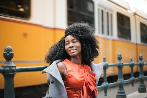 Woman in Gray Coat Standing Near Yellow Train