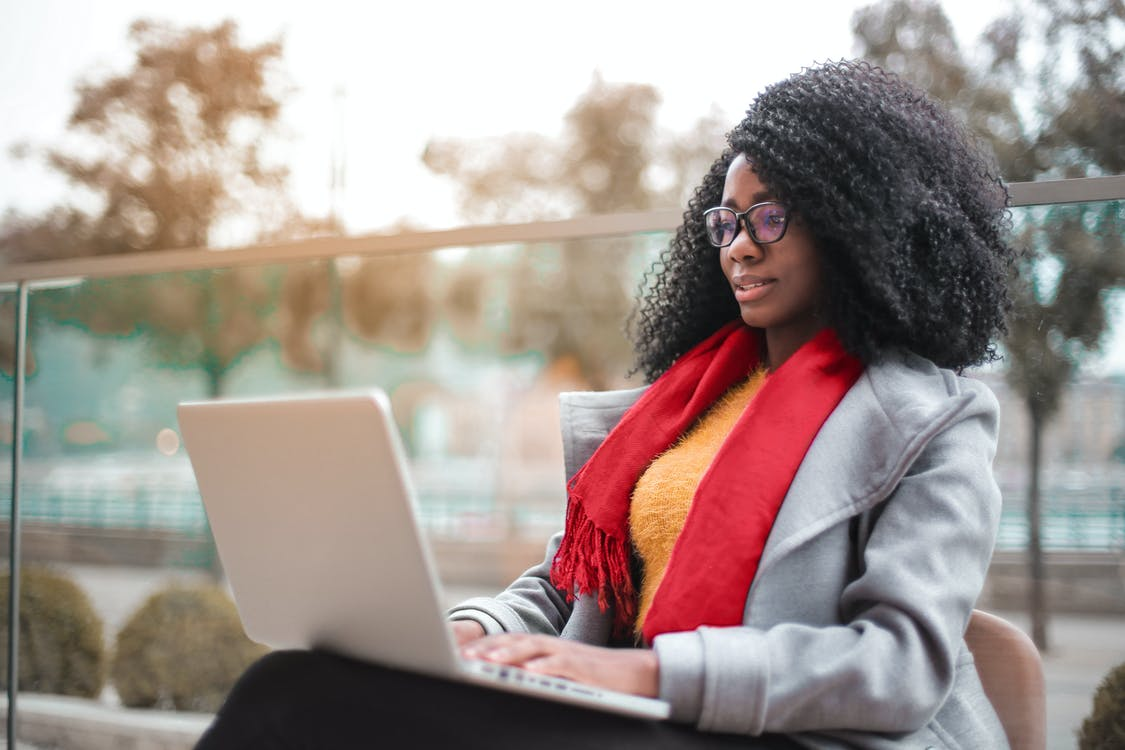 Selective Focus Photo of Woman in Gray Coat Using a Laptop