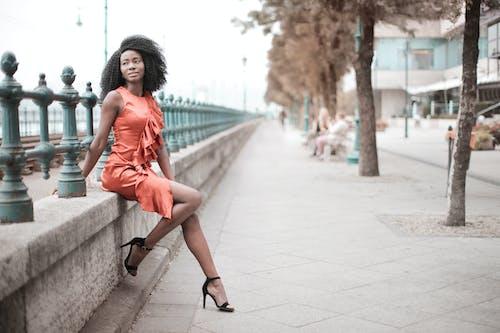 Selective Focus Photo of Woman in Orange Dress Sitting on Concrete Block