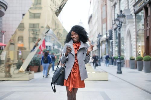 Selective Focus Photo of Woman in Gray Coat Walking while Texting and Holding Her Sunglasses