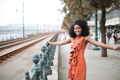Selective Focus Photo of Smiling Woman in Orange Sleeveless Dress Posing By Metal Railing