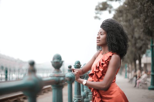 Selective Focus Side View Photo of Woman in Orange Sleeveless Dress Posing By Metal Railing