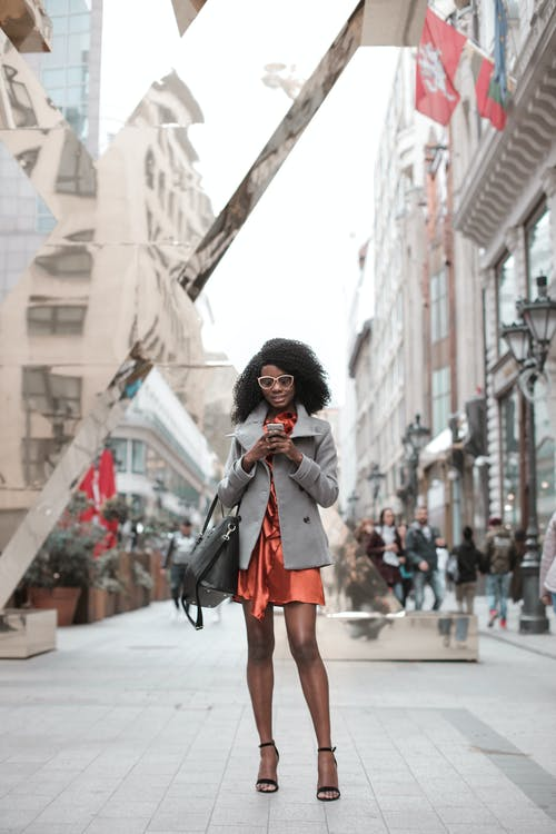 Photo of Woman in Gray Coat and Orange Dress Standing Alone While Using Her Phone