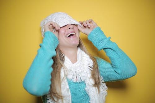 노란색 배경, 비니, 서 있는, 스웨터의 무료 스톡 사진