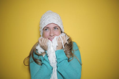 Portrait Photo of Woman in Blue Knit Sweater, White Knit Beanie, and White Scarf Smiling