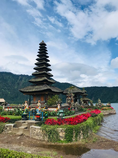 Traditional Asian pagoda on lake shore against cloudy blue sky