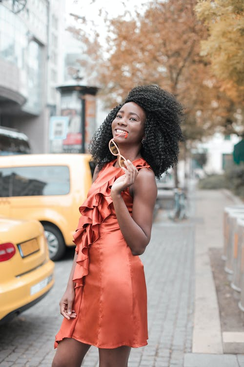 Photo of Smiling Woman in Orange Sleeveless Dress Standing on Sidewalk While Holding Glasses