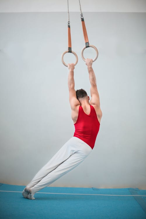Back View Photo of Male Gymnast Practicing on Gymnastic Rings