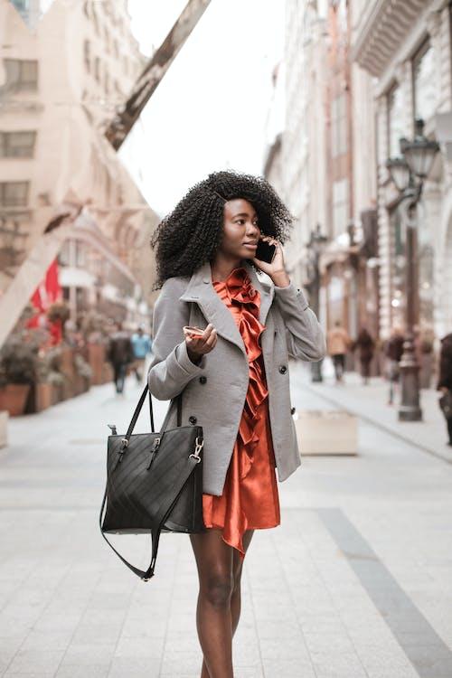 Foto Fokus Selektif Wanita Berjubah Abu Abu Memegang Kacamata Hitam Dan Membawa Tas Kulit Hitam Saat Berbicara Di Telepon