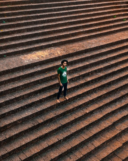 Man in Green Shirt Standing On Brown Concrete Stairs