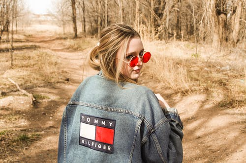 Back View Photo of Woman Wearing a Blue Denim Jacket and Red Sunglasses Looking Back