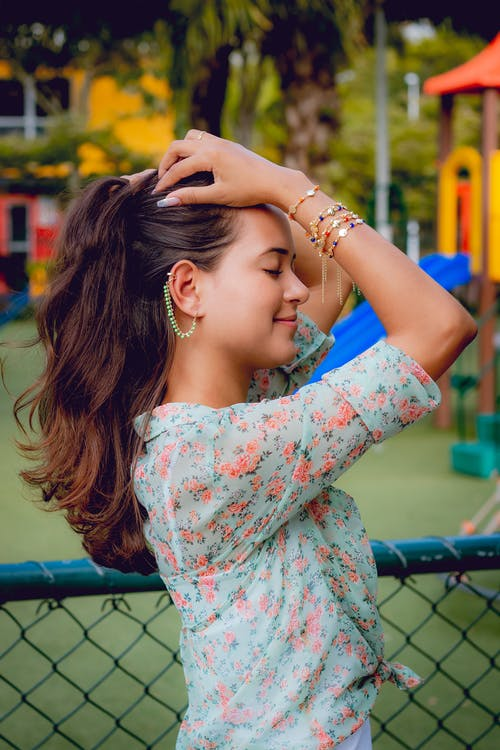 Selective Focus Side View Photo of Smiling Woman in Teal Floral Top With Her Eyes Closed Holding Her Hair While Standing Next to Chain-link Fence with Playground in the Background
