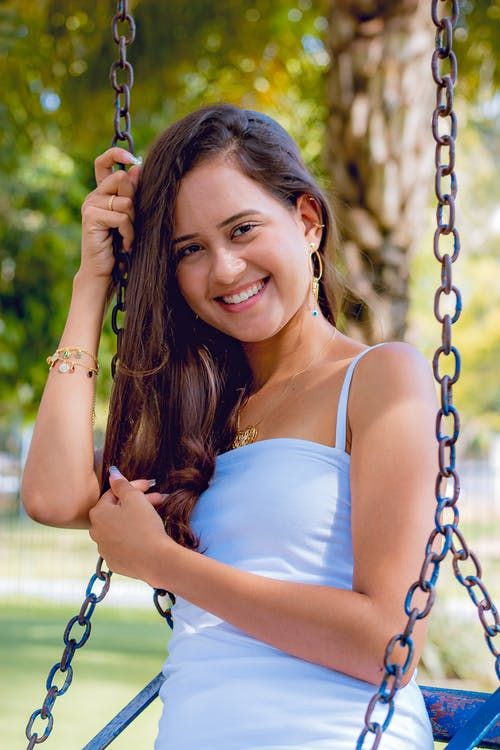 Selective Focus Photo of Smiling Woman in White Spaghetti Strap Top Sitting on a Swing