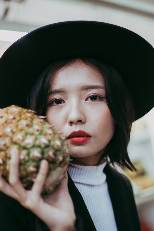 Portrait Photo of Woman in Black Hat and Coat Holding up a Pineapple