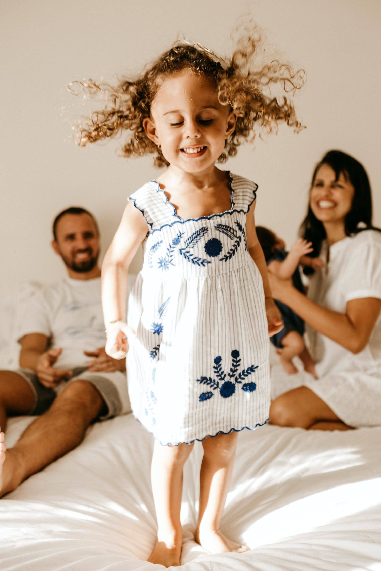 Adorable little girl with curly hair in light dress jumping on bed with closed eyes near happy young parents and newborn baby