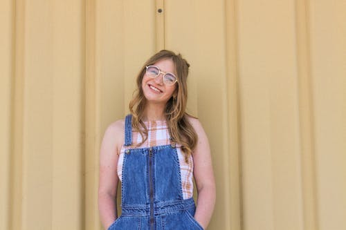 Photo of Smiling Woman in Blue Denim Dungaree and Brown Framed Eyeglasses Posing