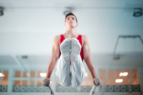 Selective Focus Photo of Male Gymnast Practicing in Gym