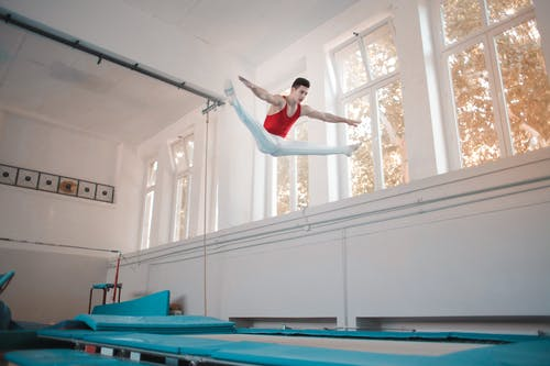 Young professional gymnast jumping on trampoline