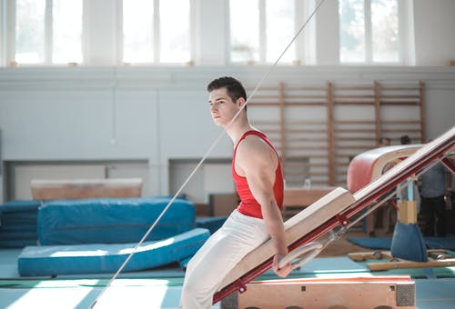 Young sportsman sitting on gymnastic equipment