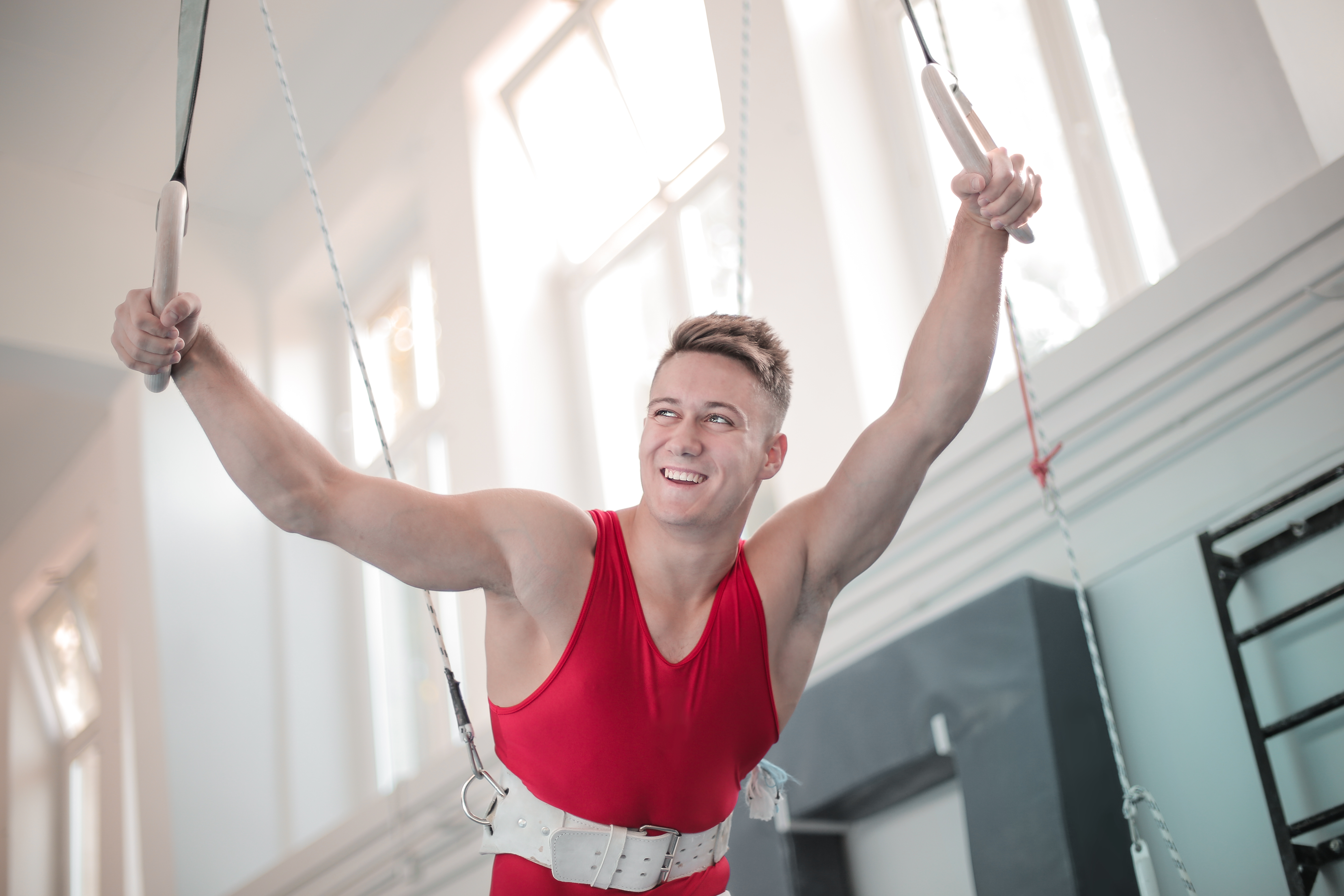 strong man in harness holding gymnastic rings