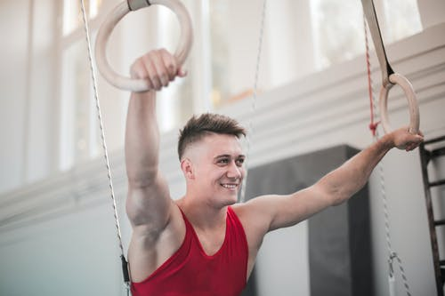 Handsome man smiling and holding gymnastic rings