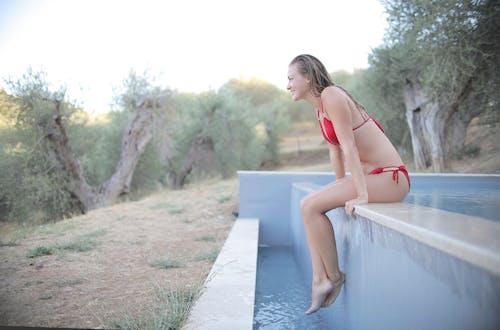 Sexy Woman in Red Bikini Sitting On Poolside