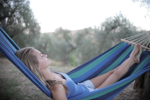 Selective Focus Photo of Woman in Blue Tank Top and Shorts Lying on a Hammock