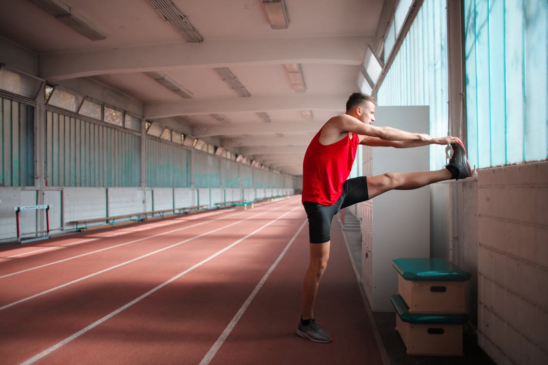 Side View Photo of Man in Red Tank Top and Black Shorts Stretching in Indoor Running Track