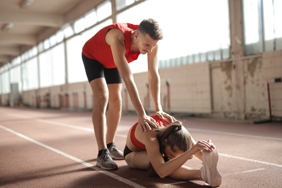 Professional male sportsman helping woman touching knees with head while female sitting on running track and doing stretching exercise