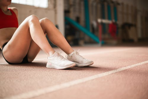 Photo of Woman in Red Tank Top, Black Shorts, and White Sneakers Sitting on Running Track