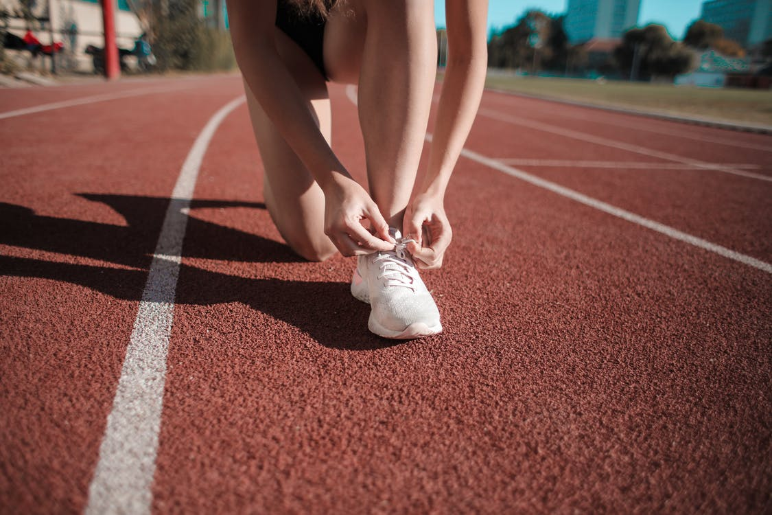 Close-up Photo of Woman Tying Her white Sneakers on Running Track