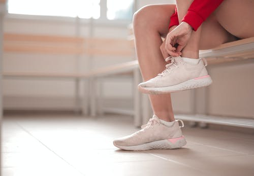 Selective Focus Photo of Person Sitting on Wooden Bench Tying Their White Sneakers