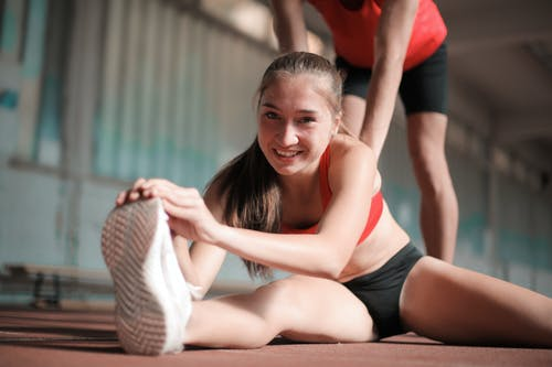 Happy sportswoman stretching legs on floor with trainer