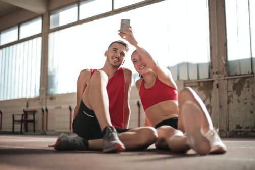 Woman in   Red Sports Bra and Black Shorts Doing Selfie