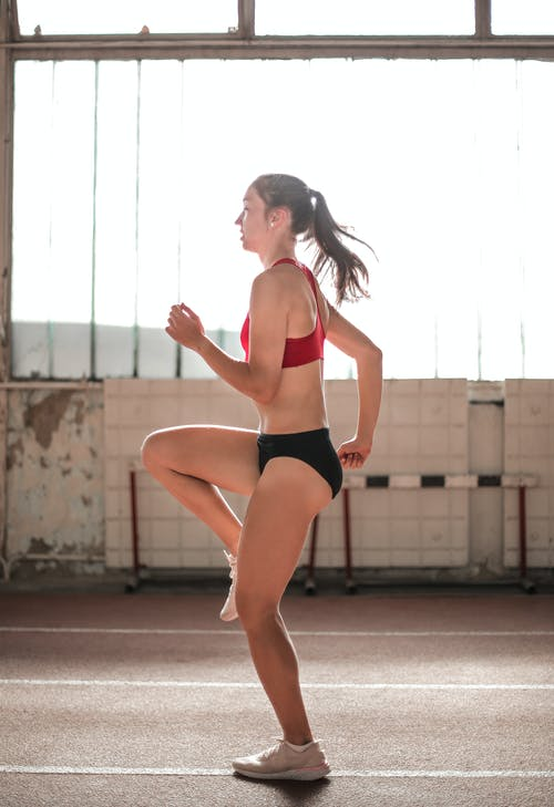 Woman in Red Sports Bra and Black Shorts Standing on Brown Concrete Floor