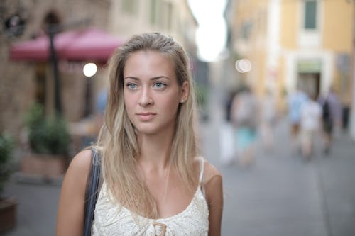 Selective Focus Portrait Photo of Woman in White Tank Top Standing on Sidewalk
