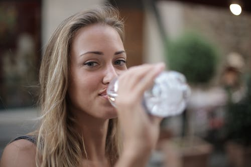 Selective Focus Photo of Smiling Woman Drinking Water from a Plastic Bottle