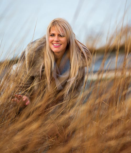 Photo of Smiling Woman in Brown Fur Coat Bending Over Brown Grass Field