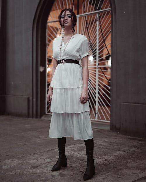 白色禮服站在牆附近的女人