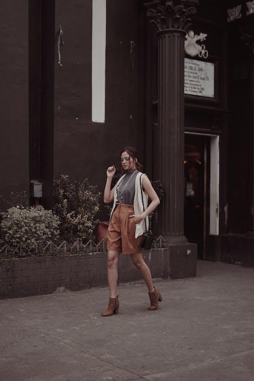 街の歩道を歩くスタイリッシュな女性