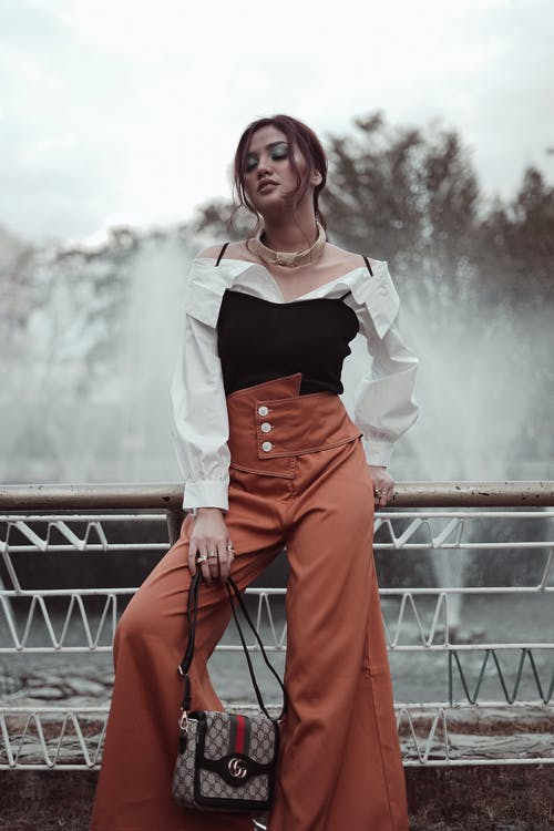 Photo of Woman in Black and White Top and Brown Trousers Posing While Leaning on Metal Railing  With Her Eyes Closed