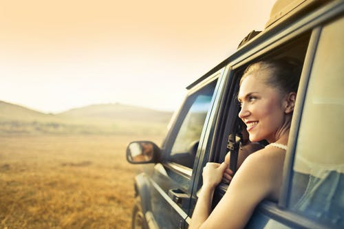 Young happy female smiling and enjoying sunset through open window while traveling by car
