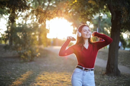 Woman in Red Long Sleeve Shirt and Blue Denim Jeans Standing on Brown Field