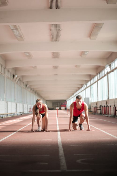 Couple of professional sportspeople ready for sprinting on empty track in training hall on sunny day